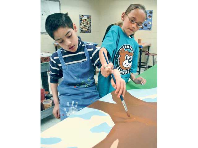 Canyon Springs Community School student Jose Quevedo, 10, left, gets a hand from fifth-grader Emma Urosevic, as they paint a section of a metal panel on Wednesday that will decorate the underpass at Golden Valley Road Bridge.