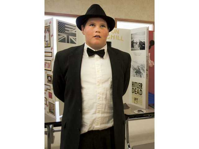 Ten-year-old Peter Christiansen, dressed as Winston Churchill, recites a short biography on the life of the former British Prime Minister.