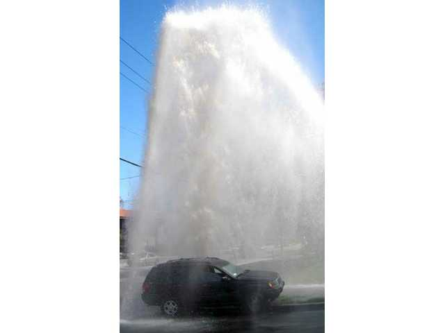 A breached fire hydrant launched thousands of gallons of water into the air after it was knocked over by a black jeep Cherokee at the intersection of Newhall Avenue and 8th street in Newhall.