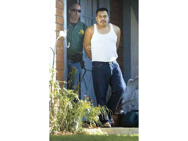 Santa Clarita Valley Sheriff's Station Detective Dan Finn walks out of a Canyon Country home with Joaquin Cruz on Wednesday morning. During a random probation and parole check, Cruz admitted to deputies hehad a small amount of illegal drugs in the bedroom he rents with wife and daughter, according to deputies.