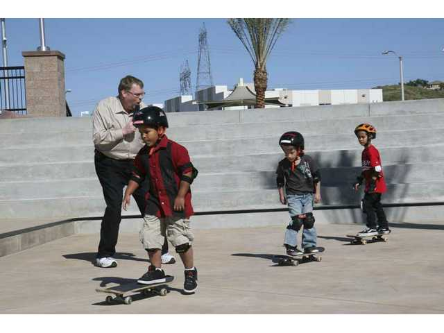 Santa Clarita Mayor Frank Ferry invites the three youngest skaters to be the very first to ride the wild concrete at the Santa Clarita Skate Park's VIP preview Thursday afternoon.