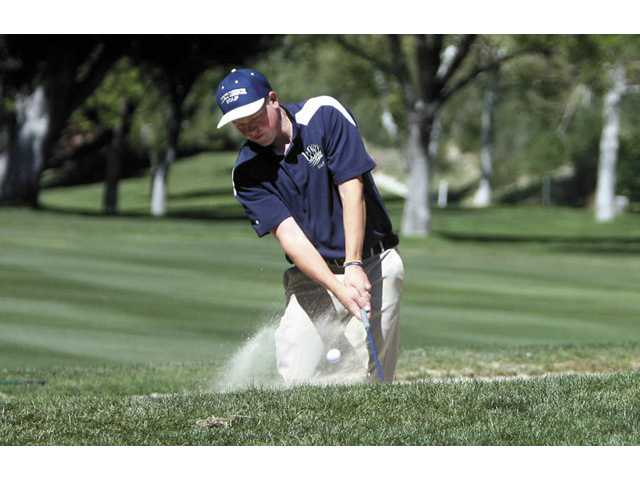 West Ranch freshman golfer J.J. Holen chips out of a sandtrap Tuesday at Valencia Country Club in the second Foothill League match. Holen shot even-par 72 to earn medalist.