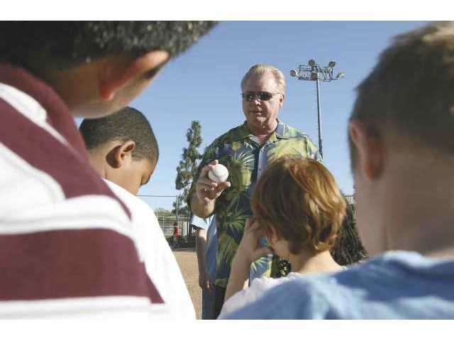 "Bill Russell, former Los Angeles Dodgers manager and shortstop from the World Champion 1981 squad, shows Santa Clarita Valley kids how to properly hold a baseball during the Boys & Girls Club's 37th annual ""A Night on the Diamond."""