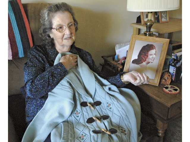 Dalpho Brazil holds a sweater her daughter Betty (in a high school senior photo by her chair) gave her as a birthday gift in 1961. Betty was killed Sept. 2, 1966, in the parking lot of Bob's Big Boy in Lakewood.