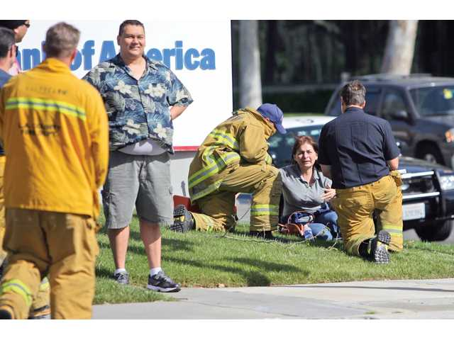 Angela Benjaro, seated, is attended to by firefighters from Station 126 after witnessing a two-car collision, as Larry Rodriguez watches his vehicle get towed.
