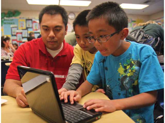 "Tesoro del Valle Elementary School fourth-grader Anson Santos, far right, shows his younger brother Aaron, a second-grader, and father, Alfred, about the computer program ""Tux Paint"" during Technology Night at the school on Thursday."