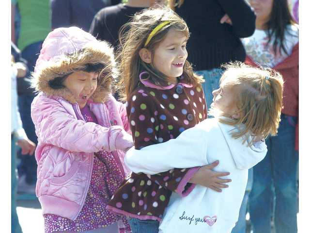 Kindergartners from left, Katelyn Tau, Isabel Ramerez and Ashley Montagna hug to keep warm Friday at Emblem Elementary School during a walk to raise money to fight cystic fibrosis.