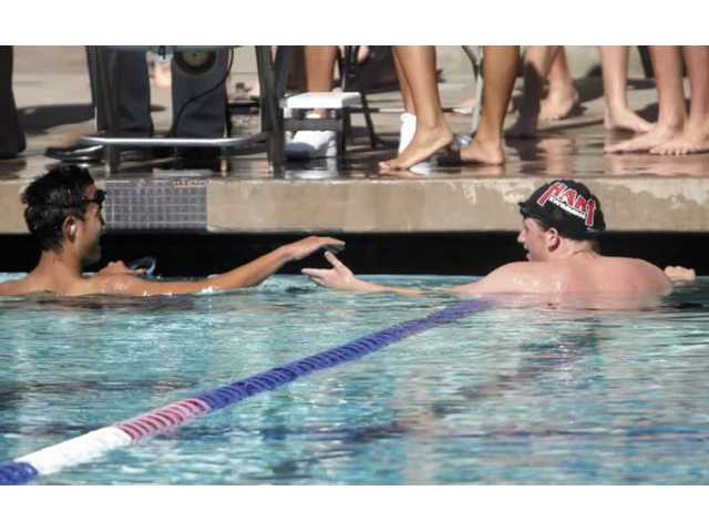 West Ranch High School's Matthew Leon shakes hands with Hart High's Ethan Goldberg at the end of the varsity 200-yard individual medley on Wednesday. Hart's boys varsity team defeated West Ranch 120-50.
