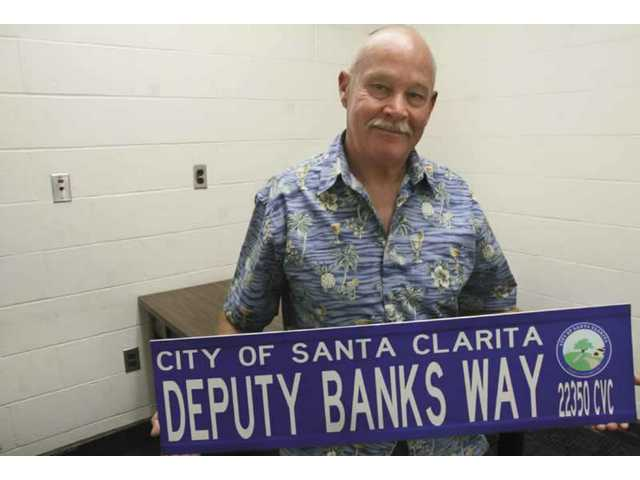 Los Angeles County Sheriff's Deputy Tommy Banks holds up a street sign given to him on his last day of work at the Santa Clarita Sheriff's Station Thursday.