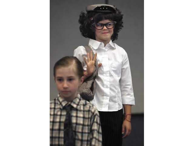 Erin Meottel, dressed as Ruth Newhall, waves to her parents in the audience during Northlake Hills Elementary School's presentation on Santa Clarita History Day. Students dressed as prominent Samta Clarita Valley residents from now and the past. Moettel's hat and purse belonged to Newhall. Sydney Brass, in plaid shirt and tie, is dressed as Scott Newhall. The Newhalls once owned The Signal.