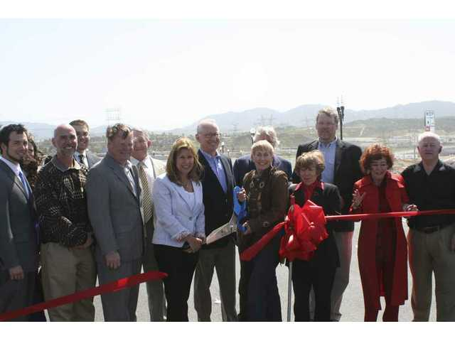 "Dignitaries lined up to cut the ribbon opening the cross-valley connector's last link. From left: Dave Perry, Antonovich Rep.; Ken Pulskamp, city manager; Scott Wilk Jr., Tony Strickland Rep.; Bob Kellar, city councilman;  Larry Rasmussen, head of Spirit Properties; Laurie Ender, city councilwoman; Congressman Howard P. ""Buck"" McKeon; Laurene Weste, mayor; Greg McWilliams, president of Newhall Land & Farming Co.; Marsha McLean, mayor pro-tem; Frank Ferry, city councilman; Connie Worden and Dennis Kootz, former council member."
