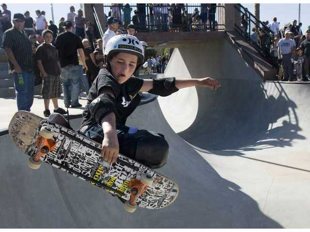 Ten-year-old Cory Frutos of West Covina shows off some moves inside the 10'-11' bowl during the grand opening of the Santa Clarita Skate Park Friday afternoon.