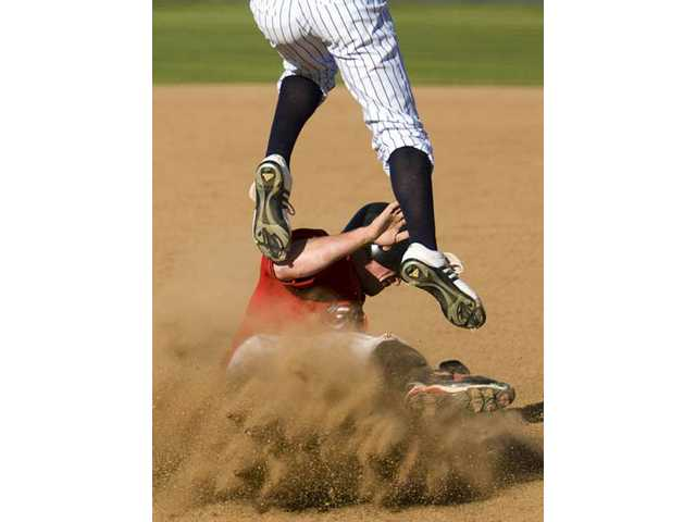 Hart's Spenser Souza slides under a Saugus player to steal his third base Friday at Hart High.