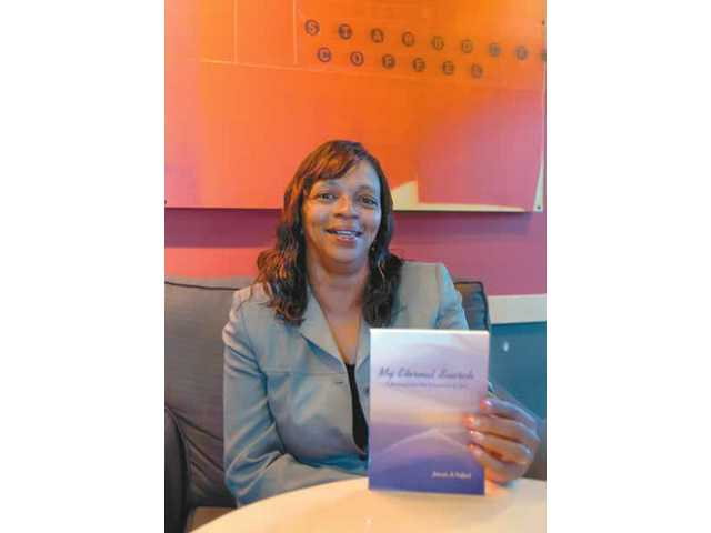 "Jolanda Tedford shows the cover her book, ""My Eternal Search: A Journey into the Tabernacle of God,"" a collection of poems that chronicles her personal journey toward better understanding God."