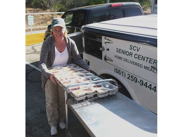 Tracy Gauny, volunteer for the Santa Clarita Valley Senior Center Home Delivered Meals program, loads up one of the center's trucks for her route. Gauny recently helped save a Newhall client's life after he collapsed and stopped breathing during her delivery.