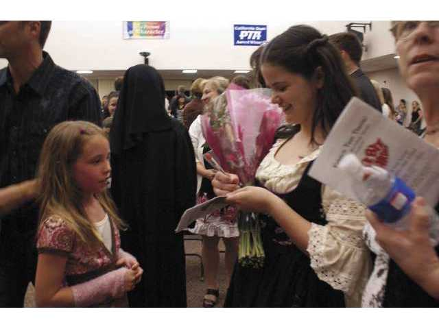 "Holly Howell signs an autograph backstage at Rio Norte Junior High School on Thursday, opening night of ""The Sound of Music."""