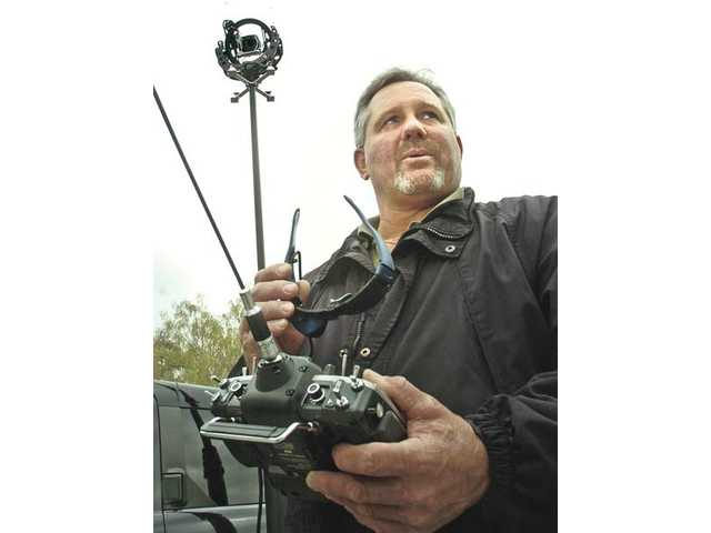 Jim Martin, creator of On-Target Aerial Services, demonstrates a remote-control aerial camera mounted on a 25-foot mast. He can see from the camera's point of view using a special glasses with a built-in display.