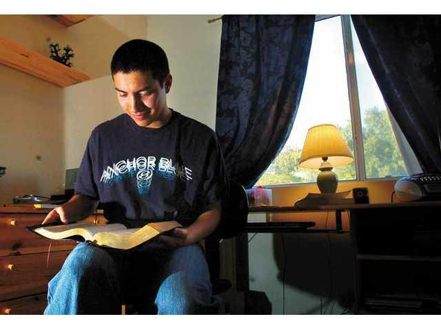 "Kevin Chu loves to read, especially ""The MacArthur Study Bible,"" which he holds here. He also enjoys video games."