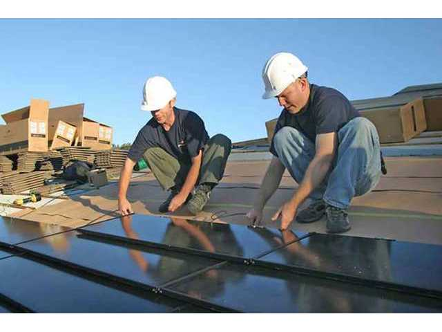 Technicians install a secton of SunTile photovoltaic solar panels on a rooftop. The panels collect sunlight, which is converted into electrical power.