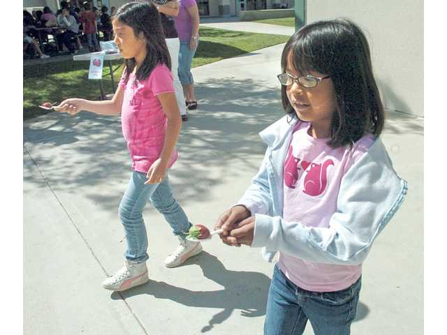 "Rachel Lim, left, and Melanie Chavez carry plastic strawberries on a spoon in the ""strawberry relay"" event as part of Health Week."