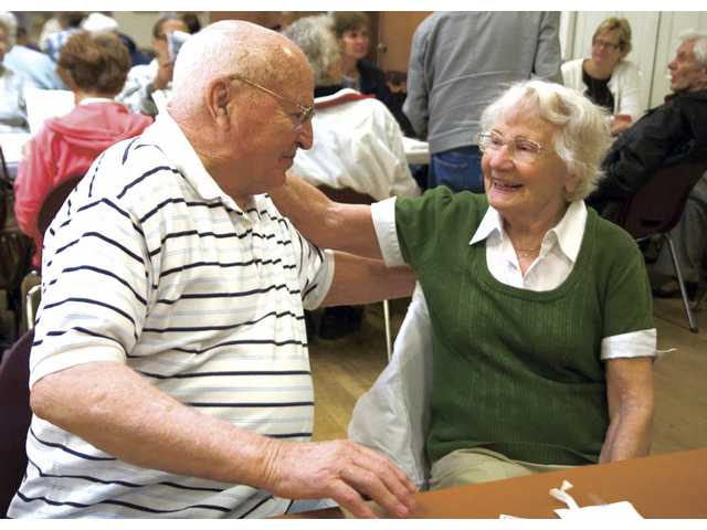 Al and Ann Cookson share a moment as they wait for their lunch at the SCV Senior Center Wednesday afternoon. The Cookson's have been married for 60 years.