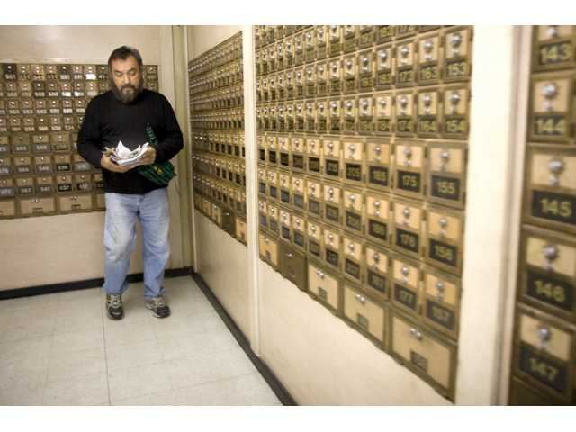 Jose Beltram, of Mission Hills, grabs his mail from his P.O. Box at the Castaic Post Office Wednesday afternoon.