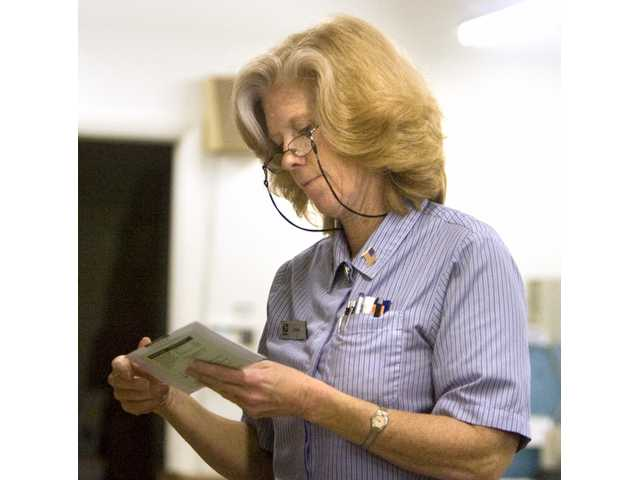 Donna Errington, a United States Postal Service Employee for 28 years, sorts out mail at the Castaic Post Office Wednesday afternoon. The post office will relocate to a new space Saturday. The new location at 28201 Franklin Parkway has the capacity for three times more post office boxes than the current location.