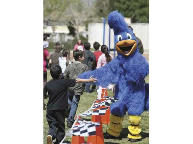 Rosie the Roadrunner, mascot for Rosedell Elementary, high-fives students as they complete laps for Monday's jog-a-thon.