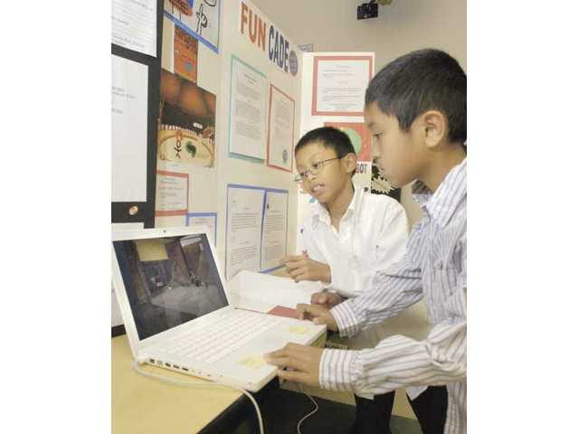 Fifth-grader Jomar Basuyot, center, explains the marketing plan for 'Fun Cade,' a game arcade business, to his brother Jeron, 9.