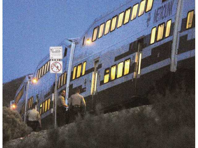 L.A. County Sheriff's deputies prepare to board a Metrolink train stopped between Canyon Country and Acton to interview passengers after the train struck and killed a man standing on the railroad tracks early Tuesday evening.