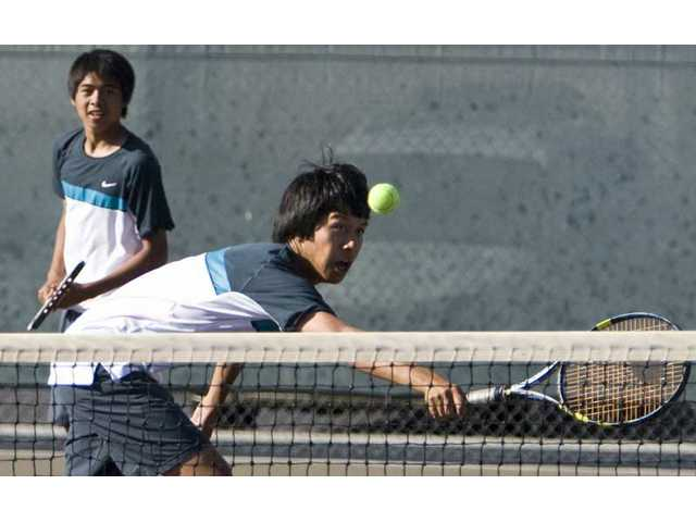 West Ranch's Jeremy Ramirez stretches to return the tennis ball Tuesday at Golden Valley High as teammate Julius Macalutas watches on.