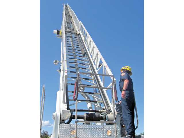 The fire truck operator extends the truck's aerial ladder to accommodate off-duty firefighters an all-day seminar on the physics of an aerial ladder held at the Hyatt in Valencia on Thursday.