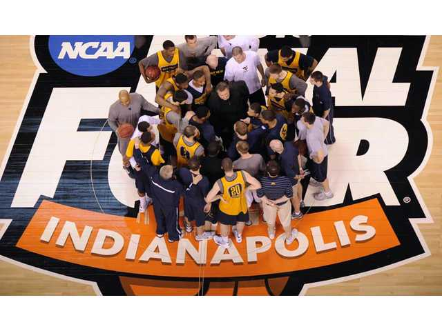 West Virginia players huddle on the court during a practice session for the NCAA Final Four college basketball tournament Friday, April 2, in Indianapolis. West Virginia faces Duke Saturday in a semifinal game.