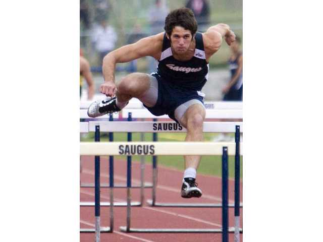 Saugus senior Cameron Penta jumps a hurdle in the 110 meter race Thursday at Saugus High Thursday. Penta won the 110 and 300 meter events.