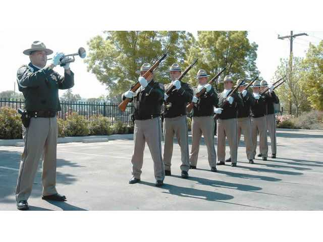 The California Highway Patrol memorial drill team performs a 21 gun salute Friday in Santa Clarita during the memorial and dedication for the four CHP officers killed 38 years ago.