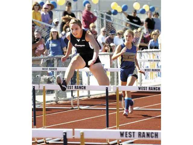 Saugus High's Allison Rudd clears a hurdle on her way to victory in the 100 race against West Ranch on Thursday. Rudd won the event with a time of 16.10. She also claimed the 300 hurdles in 48.3 as her Centurion team defeated the Wildcats 111-25.