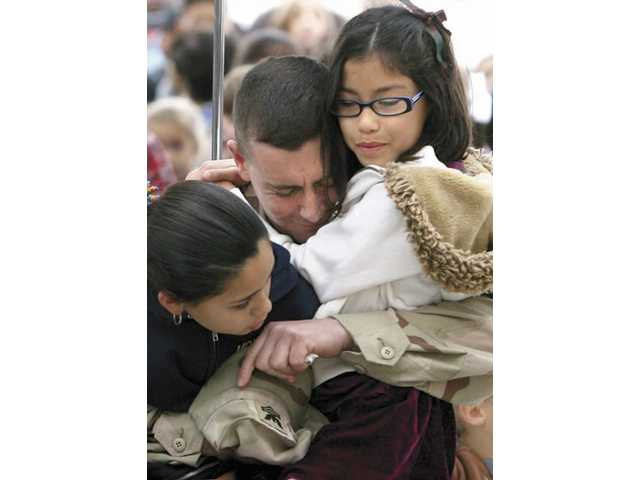 Travis Peterson hugs his daughters Antionette, left, and Elizabeth during an assembly at Mountainview Elementary on Thursday morning after surprising them with a visit home from his service in Afghanistan. Peterson, a Navy information technician, is on a 15-day leave after serving seven months in Kabal, Afghanistan.