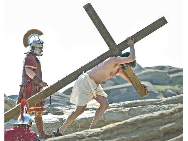 Roman soldiers whip Jesus (Adam Granger), as he carries his cross to the top of a hill for crucifixion, during the Easter Pageant presented at Vasquez Rocks by the Alliance of Christian Churches of Acton and Agua Dulce on Saturday. There will also be a 5 a.m. performance today for Easter Sunday.