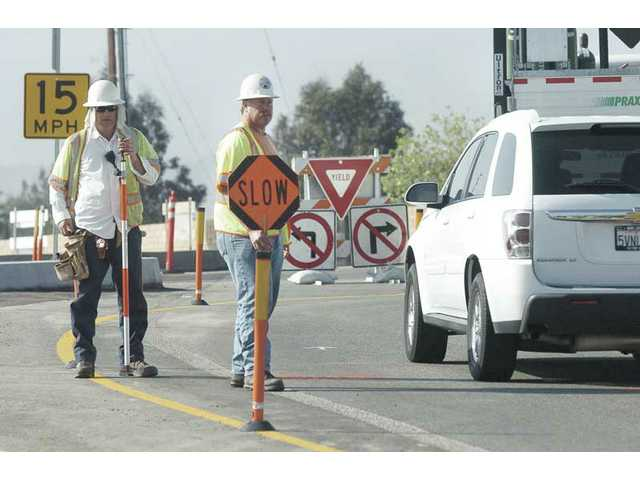 Workmen slow traffic as they do survey work on the roundabout at Hasley Canyon and The Old Road on Thursday.