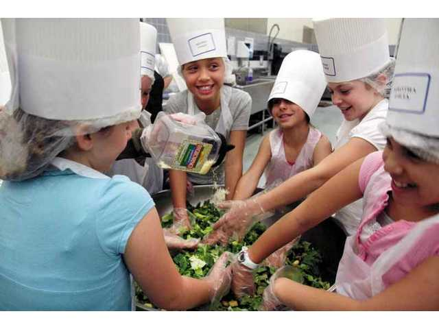 A group of Mountainview Elementary School fourth-graders help toss the Caesar salad on Thursday at the SCV School Food Services Agency.