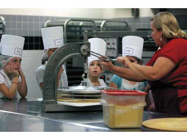 Cindy Turner, nutritional assistant at the SCV School Food Services Agency, demonstrates how pizzas are made and sliced with a special machine. The students are from Miss Dabbeekeh's class.