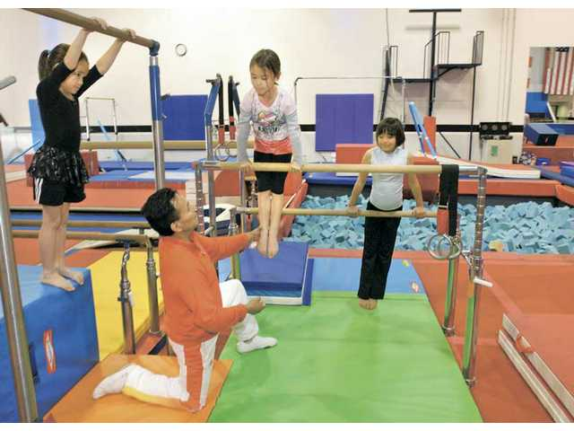 Hugo Cherre, kneeling, works with Kendall De La Vega, 7, left, Zenaida McKinney, 7, and Victoria Del Rosario, 8, on Friday as they train on the uneven bars in front of the dismount pit. Cherre's athletic facility for children, Hugo's Gymfitness, is still awaiting planning commission approval.