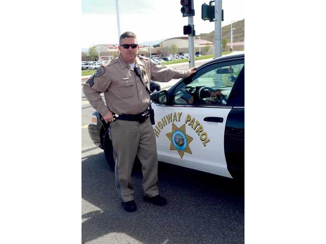 "CHP Sergeant Rick Miler stands by his patrol vehicle near West Ranch High School in Stevenson Ranch. Miler was one of several CHP officers who took part in the ""Every 15 Minutes"" program held recently at the school."