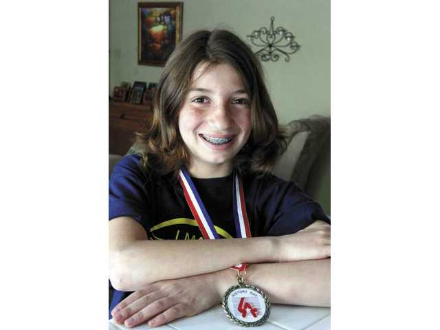 Castaic Middle School student Jessica Resnick, 11, wears the medal she won in an L.A.-wide history competition for her project on a Japanese-American who avoided internment during World War II.