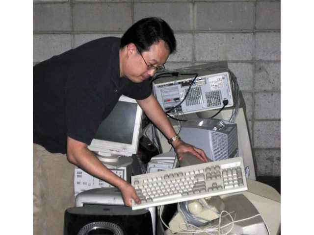 Joe Choo, The Signal's IT/interactive manager, adds to the collection of old computers that will no longer be used by the newspaper, which is switching over to a new computer system. Often, old-but-functioning computers can be reused. Otherwise they should be recycled.