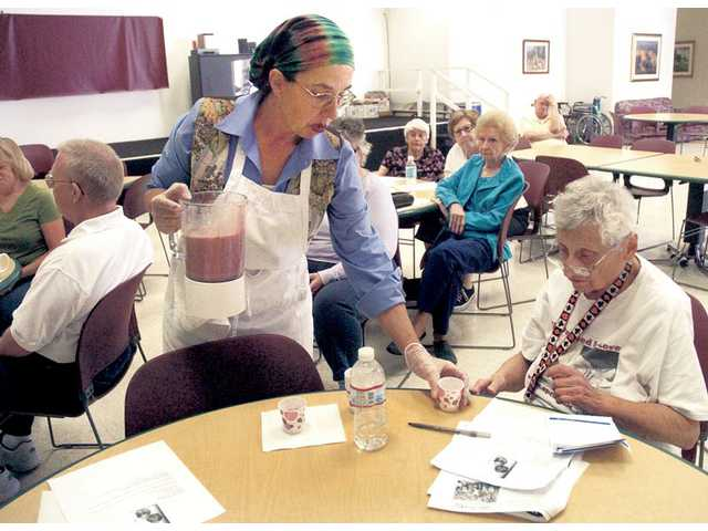 Registered dietitian Stephanie Correnti pours a sample of her pomegranate smoothie for seniors as they look over the recipe during a cooking class at the Bouquet Canyon Senior Apartments on Friday. Correnti will present recipes every Friday until April 23.