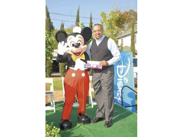 Jim Ventress, chief professional officer of the Boys & Girls Club of Santa Clarita Valley, accepts a $5,000 donation from Mickey Mouse in Disneyland last week.