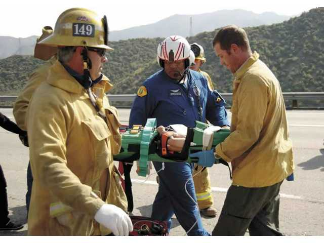 L.A. County firefighters carry an injured child to a waiting helicopter on Saturday afternoon. The nine-month-old child was ejected from the car it was riding in after the vehicle blew a tire and hit the median rail while traveling southbound on Interstate 5 near Pyramid Lake.