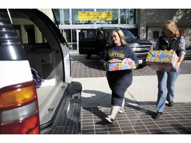 Allison Devlin, director of student development at COC, left, and Anita Seibert, outreach program coordinator for the Michael Hoefflin Foundation, load up an SUV full of wishes to be delivered Saturday morning.