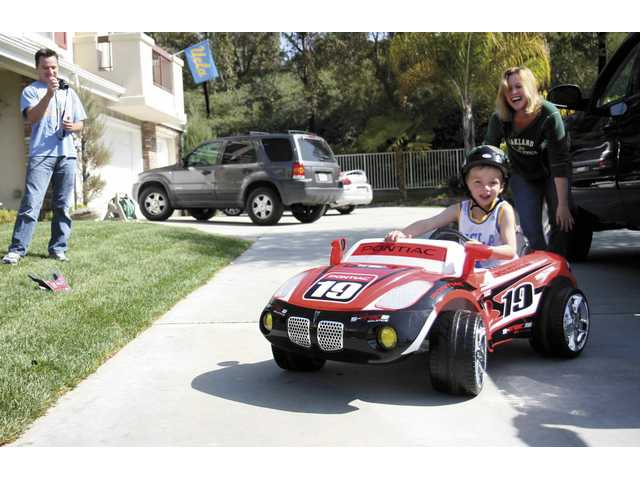 Tyler Cordova, 5, from Valencia, drives off in his new Pontiac power wheel car, as his parents Derek and Holly Cordova watch him on Saturday morning.
